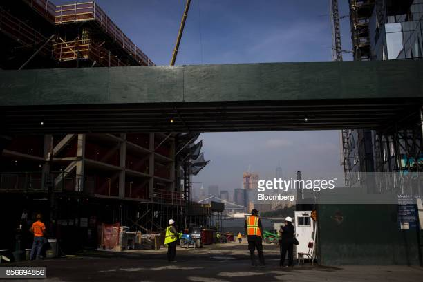 Workers stand between 420 and 416 Kent Avenue apartment developments under construction in the Williamsburg neighborhood of the Brooklyn borough of...