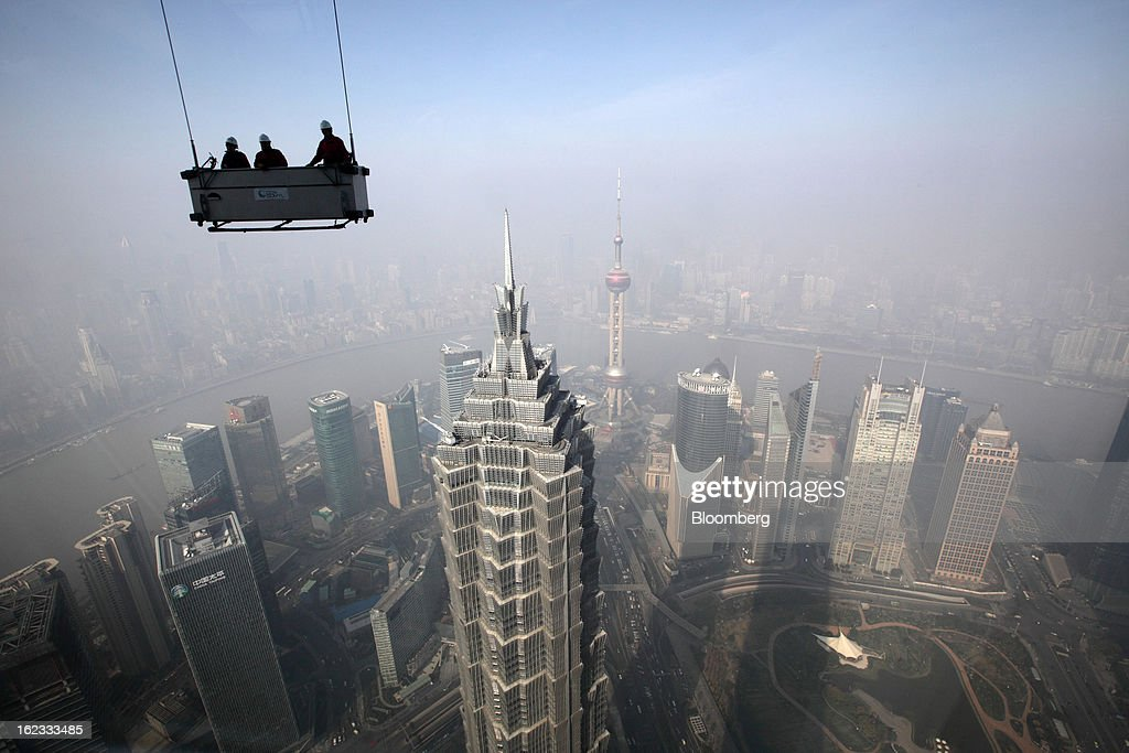 Workers stand in a suspended platform ready to clean windows at the Shanghai World Financial Center in the Pudong area of Shanghai, China, on Wednesday, Jan. 30, 2013. China's economic growth accelerated for the first time in two years as government efforts to revive demand drove a rebound in industrial output, retail sales and the housing market. Photographer: Tomohiro Ohsumi/Bloomberg via Getty Images