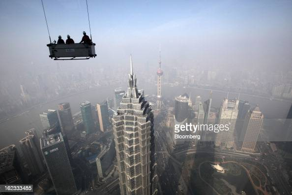 Workers stand in a suspended platform ready to clean windows at the Shanghai World Financial Center in the Pudong area of Shanghai China on Wednesday...