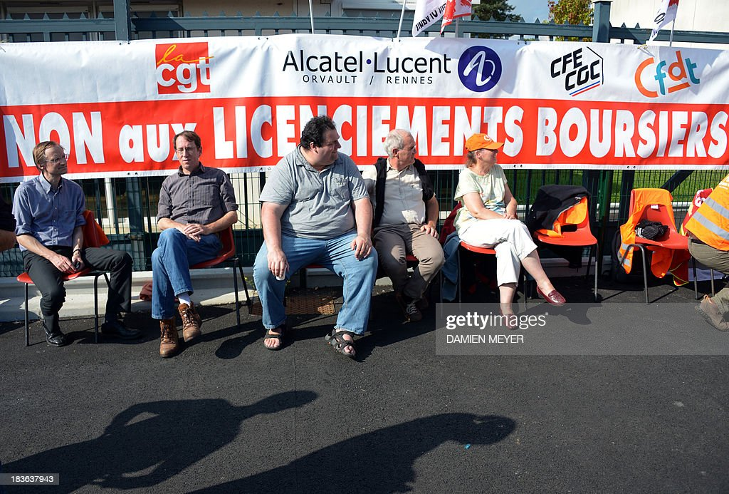 Workers stand in front of a CGT trade union banner reading : 'No to layoffs due to market forces' on October 8, 2013 in Orvault, western France, in front of a plant of French-US telecom-equipment maker Alcatel-Lucent, after the group announced the cut of 10,000 jobs worldwide to reduce fixed costs by 15 percent in two years, the company announced on October 8, 2013. The company said that 4,100 jobs would be cut in Europe, the Middle East and Africa by 2015, 3,800 in the Asia Pacific region, and 2,100 in North and South America.