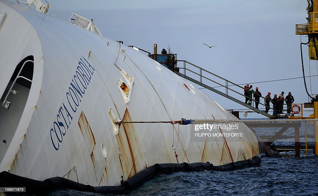 Workers stand in front of the Costa Concordia cruise ship laying aground outside the port the western Italian island of Giglio on January 12, 2013. A year after the Costa Concordia tragedy in which 32 people lost their lives, the giant cruise ship still lies keeled over on an Italian island and its captain Francesco Schettino has become a global figure of mockery.