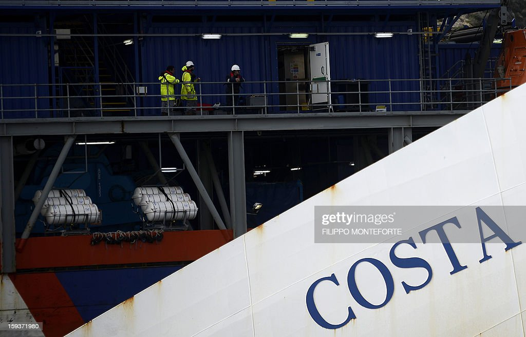 Workers stand in front of the Costa Concordia cruise ship laying aground outside the port the western Italian island of Giglio on January 12, 2013. A year after the Costa Concordia tragedy in which 32 people lost their lives, the giant cruise ship still lies keeled over on an Italian island and its captain Francesco Schettino has become a global figure of mockery. AFP PHOTO / FILIPPO MONTEFORTE