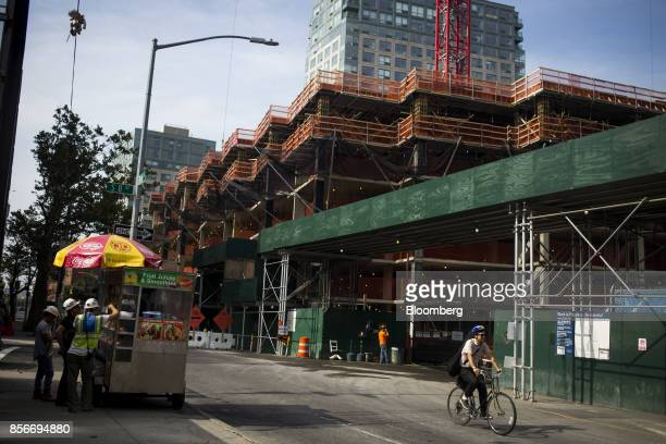 Workers stand in line at a food vendor outside the 420 Kent Avenue apartment development under construction in the Williamsburg neighborhood of the...