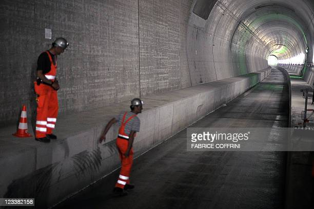 Workers stand in one of the Gotthard base access tunnels during the launching of the installation of railway equipment on September 2 2011 in...