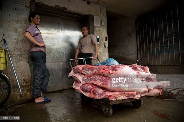 Workers stand near a cart laden with pig carcasses in the Gongbei district of Zhuhai Guangdong province China on Sunday Nov 16 2014 Investors piled...