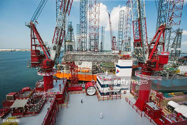 Workers stand near cranes on a deck onboard a Floatel International Ltd semisubmersible accommodation built and developed by Keppel Offshore Marine...