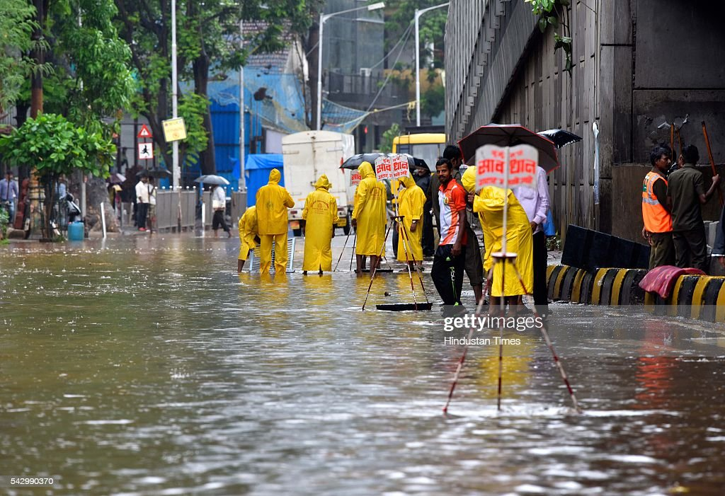 BMC worker stand near open manhole on water logged street at Parel, on June 24, 2016 in Mumbai, India. Rains continued to lash Mumbai for the third consecutive day today, slightly disrupting suburban train services, even as the Met department predicted heavy showers. India Meteorological Departments Regional Meteorological Centre in Mumbai predicted intermittent rain with heavy to very heavy rainfall at a few place in the city and its suburbs for the next 24 to 48 hours.
