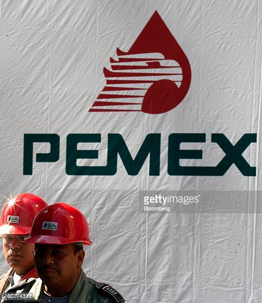 Workers stand next to a banner with the Petroleos Mexicanos logo on it at the blast site at company headquarters in Mexico City Mexico on Tuesday Feb...