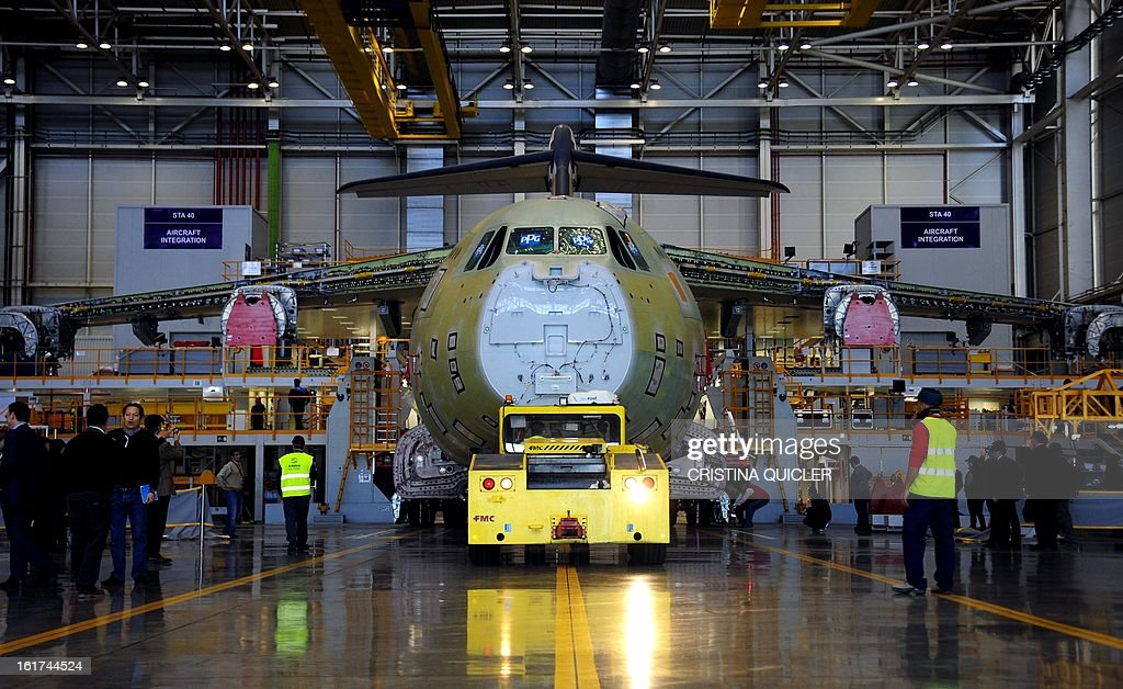 Workers stand next to an Airbus Military A400M transport plane under construction in the factory at San Pablo-Airbus Military in Sevilla on February 15, 2013. The four-engine aircraft was designed to replace C-130 Hercules and C-160 Transall cargo planes, and can perform three major roles, according to Airbus, including tactical missions that require the ability to land at 'austere airfields' such as soft or rough strips as short as 750 metres (2,500 feet) with a payload of up to 25 tonnes (55,000 pounds).