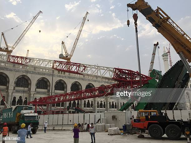Workers stand next to the crane that collapsed the day before at the Grand Mosque on September 12 2015 in Saudi Arabia's holy Muslim city of Mecca...