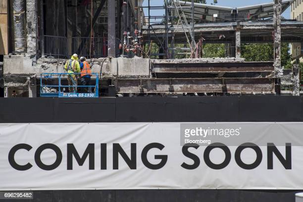 Workers stand on a cherry picker above a 'Coming Soon' sign displayed at a building under construction in Sacramento California US on Tuesday June 6...