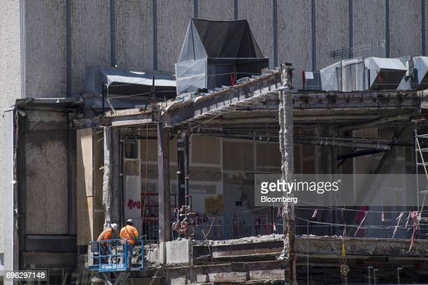 Workers stand on a cherry picker next to a building under construction in Sacramento California US on Tuesday June 6 2017 As the cost of daily life...