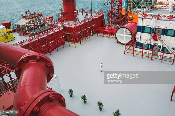 Workers stand on a deck onboard the Floatel Triumph a semisubmersible accommodation rig operated by Floatel International Ltd and developed by Keppel...
