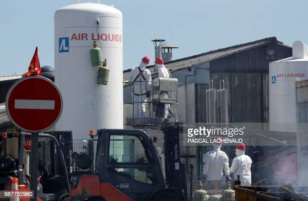 Workers stand on a lifting ramp to take gas cylinders off an Air Liquide gas holder at the site of ailing car parts factory GmS Industry factory in...