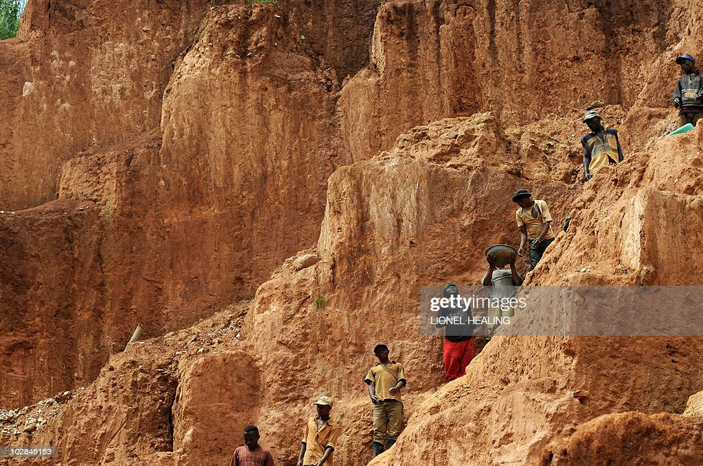 Workers stand on a muddy cliff as they work at a gold mine on February 23 2009 in Chudja near Bunia north eastern Congo The conflict in the Congo has...