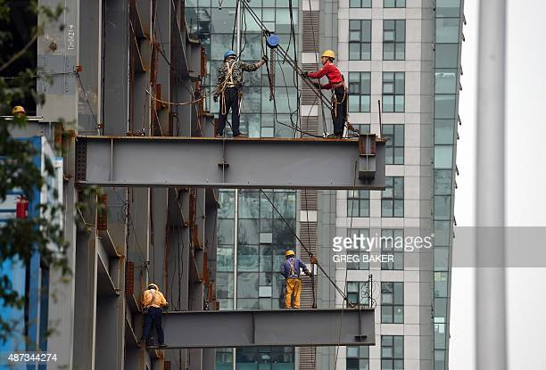 Workers stand on beams on a construction site in Beijing on September 9 2015 China's government says the world's second largest economy is expanding...