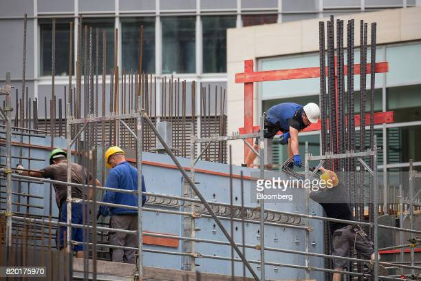 Workers stand on scaffolding at a building construction site in Frankfurt Germany on Thursday July 20 2017 Frankfurt has emerged as a winner of the...