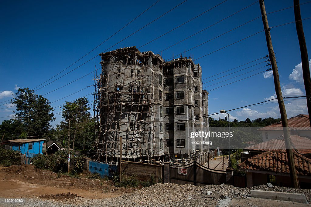 Workers stand on scaffolding beside a new residential apartment block under construction in Nairobi, Kenya, on Friday, March 1, 2013. Next week's presidential vote will be the first since disputed elections in 2007 triggered ethnic fighting in which more than 1,100 people died and another 350,000 fled their homes. Photographer: Trevor Snapp/Bloomberg via Getty Images