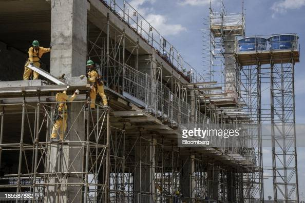 Workers stand on scaffolding during construction of Terminals 3 and 4 at the Sao Paulo/Guarulhos Governor Andre Franco Montoro International Airport...