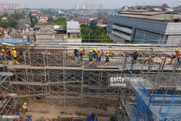 Workers stand on scaffolding during the construction of an elevated track for the Jakarta Mass Rapid Transit in this aerial photograph taken in...