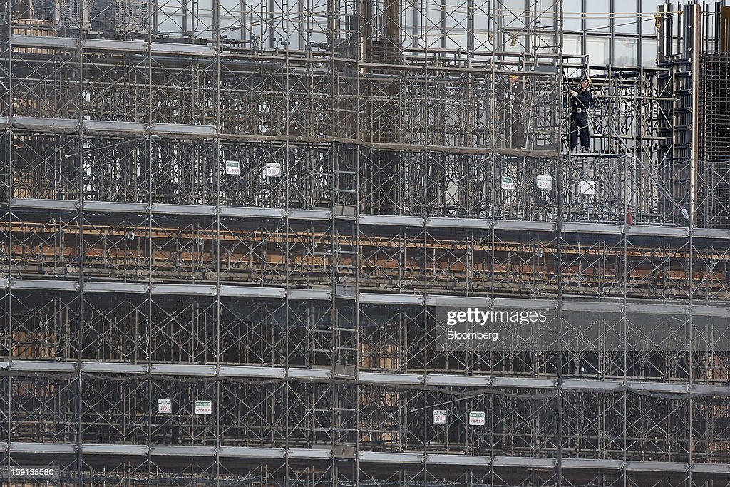 Workers stand on scaffolding on a construction site for a hospital in Tokyo, Japan, on Tuesday, Jan. 8, 2013. Prime Minister Shinzo Abe aims to compile Japan's economic stimulus package on Jan. 11, and seeks to have new economic growth strategy by mid-year. Photographer: Kiyoshi Ota/Bloomberg via Getty Images