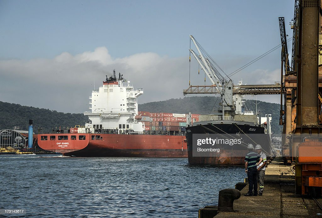 Workers stand on shore as a container ship departs the Port of Santos in Santos, Brazil, on Friday, July 5, 2013. Rising borrowing costs and the global bond selloff triggered by the prospect of reduced U.S. stimulus are prompting Brazilian investors to boost holdings of the countrys floating-rate securities. Photographer: Paulo Fridman/Bloomberg via Getty Images
