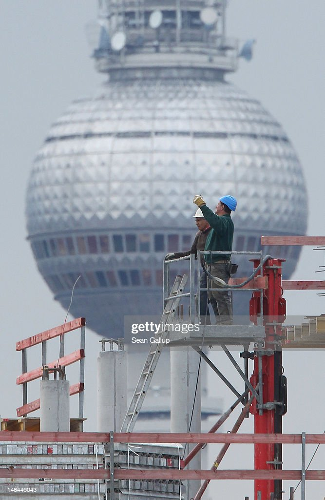 Workers stand on the construction site of a new office building as the broadcast tower at Alexanderplatz stands behind on July 16, 2012 in Berlin, Germany. Construction sites are common across the city as developers invest in new projects, especially in east Berlin, where there are still large amounts of open space.