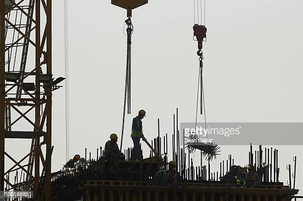Workers stand on the construction site of a new office building in the budding new financial district on October 23 2011 in Doha Qatar Qatar will...
