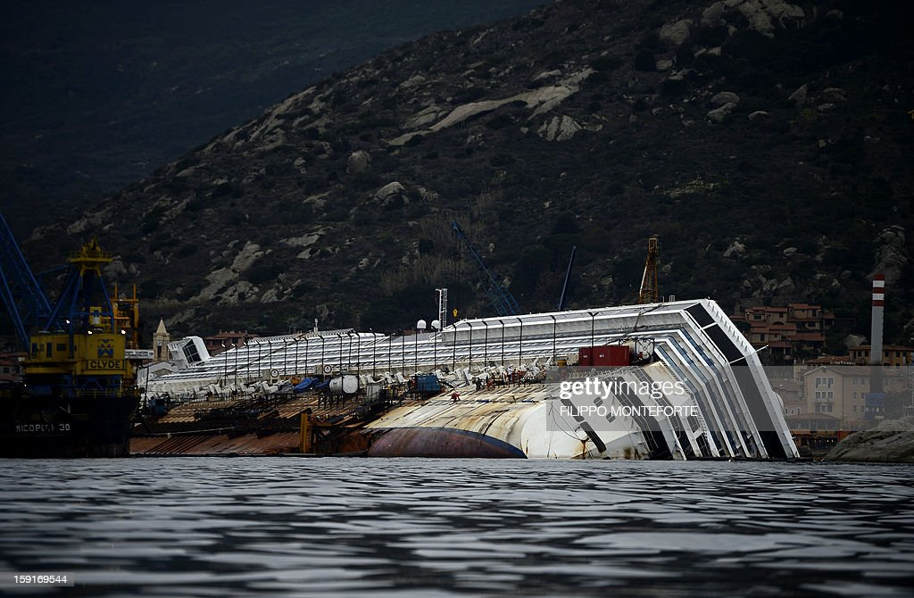 Workers stand on the Costa Concordia cruise ship laying aground near the port on January 9, 2013 on the Italian island of Giglio. A year on from the Costa Concordia tragedy in which 32 people lost their lives, the giant cruise ship still lies keeled over on an Italian island and its captain Francesco Schettino has become a global figure of mockery.