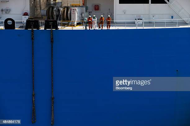 Workers stand on the deck of the Tangguh Palung liquefied natural gas tanker operated by Tangguh LNG as it approaches the Korea Gas Corp LNG terminal...