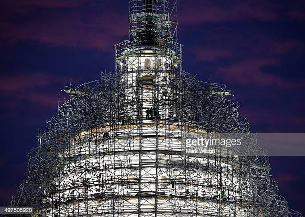 Workers stand on the scaffolding that surrounds the dome of the US Capitol which is undergoing restoration November 17 2015 in Washington DC The...