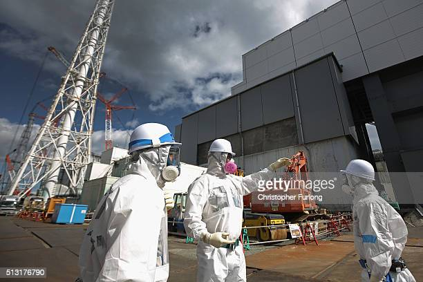 Workers stand outside reactor 4 as they continue the radiation decontamination process at the Tokyo Electric Power Co's embattled Fukushima Daiichi...