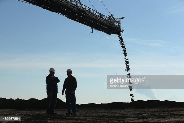 Workers stand under a a mobile machine called a spreader depositing soil removed from one end of the Welzow Sued openpit lignite coal mine to allow...