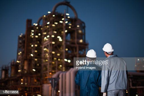 Workers standing at oil refinery