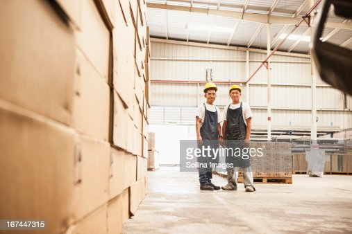 Workers standing in manufacturing plant : Stock Photo