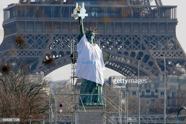 Workers standing on scaffolds erected around the replica Statue of Liberty by French sculptor Auguste Bartholdi install a giant white tshirt on March...