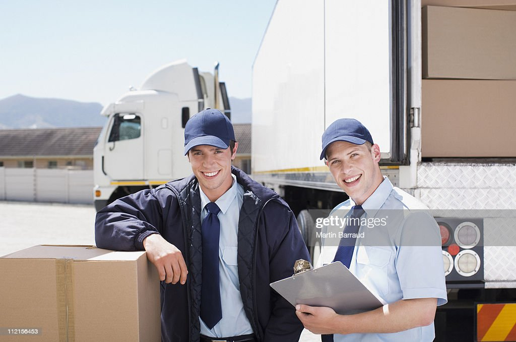 Workers standing with boxes near semi-truck : Stock Photo