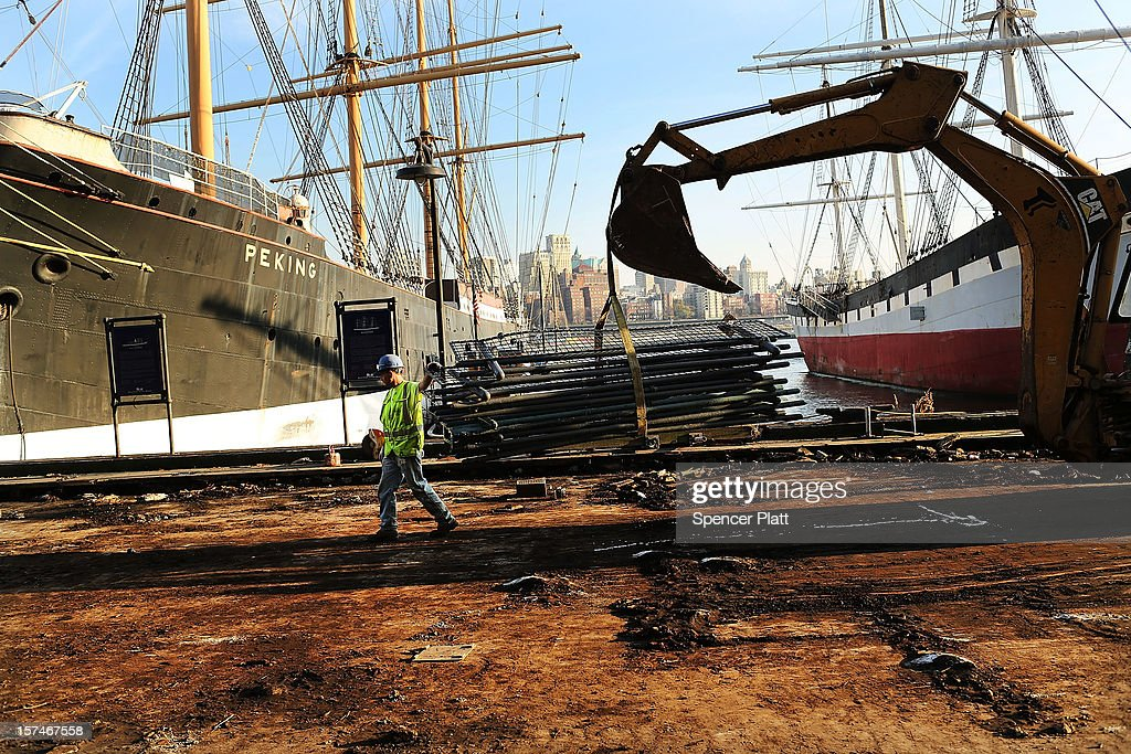 A workers stands on a flood damaged pier affected by Superstorm Sandy at South Street Seaport on December 3, 2012 in New York City. South Street Seaport, an area popular with tourists which was about to go through a major redevelopment, suffered severe damage from Hurricane Sandy. Most of the buildings and businesses, including the South Street Seaport Museum, suffered severe flooding and remained closed. According to a new Siena Research Institute poll, most New Yorkers overwhelmingly agree that climate change was behind Hurricane Sandy.