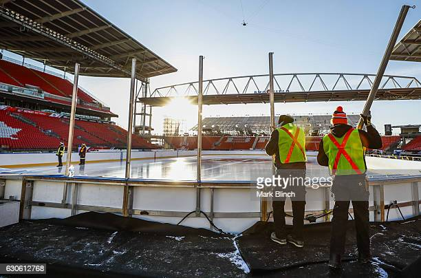 Workers start to install the glass during the build out of the outdoor rink for the 2017 Scotiabank NHL Centennial Classic between the Detroit Red...