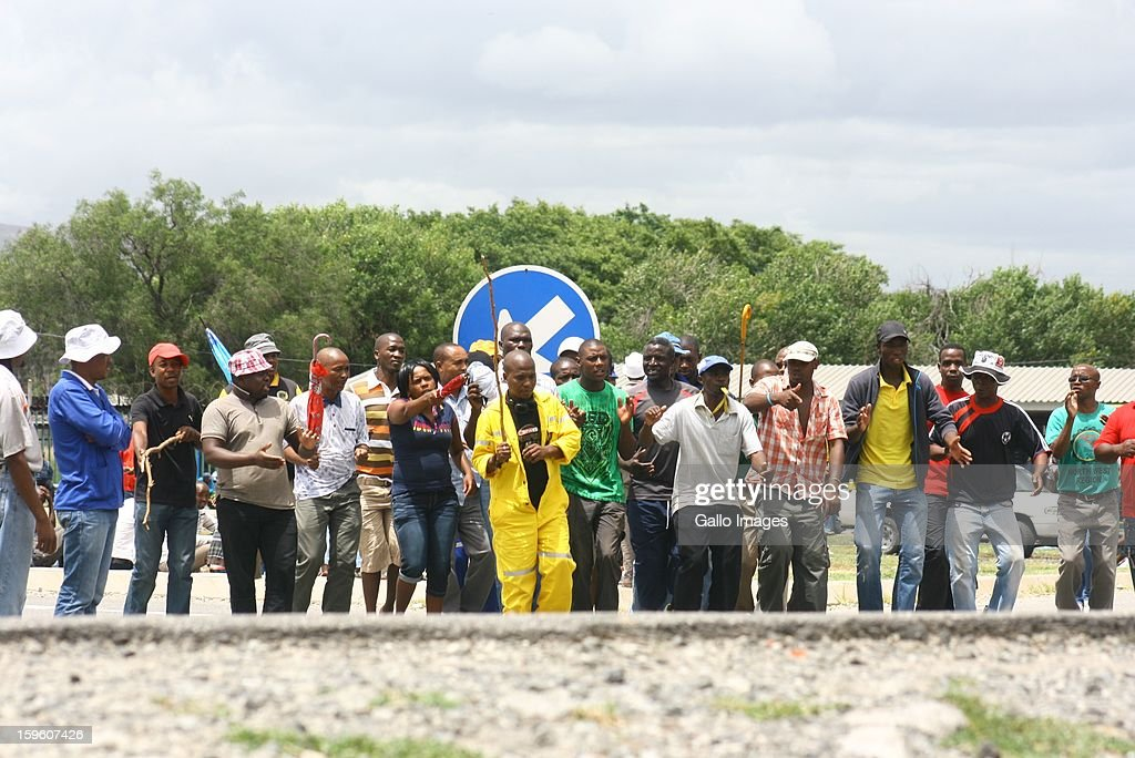Workers strike outside the Khomanani Mine on January 16, 2013 in Rustenburg, South Africa. Anglo American Platinum workers are refusing to work after the company announced that 14,000 jobs could be lost during a major restructuring of the company.