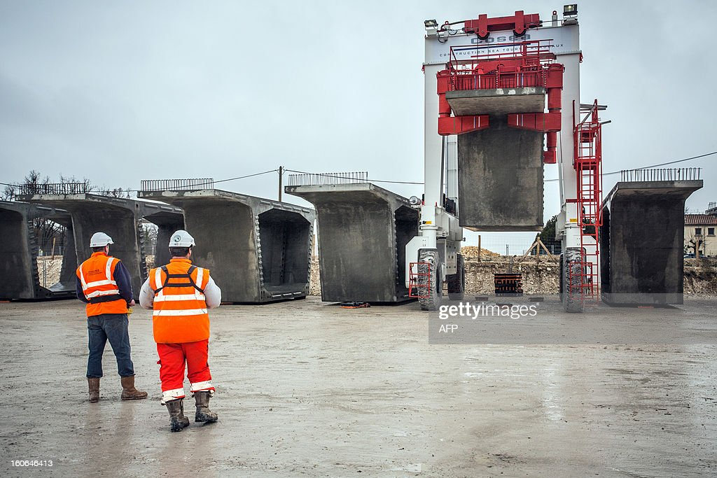 Workers supervise the installation of the first voussoirs at a building site of the Tours-Bordeaux LGV high speed train line on February 4, 2013 in Roullet-Saint-Estephe. AFP PHOTO PIERRE DUFFOUR