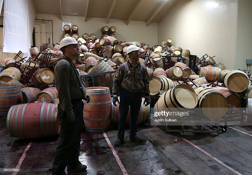 Workers survey a mound of toppled wine barrels that sit in a storage room at Kieu Hoang Winery on August 25, 2014 in Napa, California. A day after a 6.0 earthquake rocked the Napa Valley, residents and wineries are continuing clean up operations.