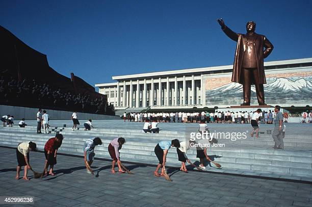 Workers sweep the ground on in front of the Grand Monument a bronze statue of Kim Il Sung on Mansu Hill in Pyongyang Kim Il Sung was the pseudonym...