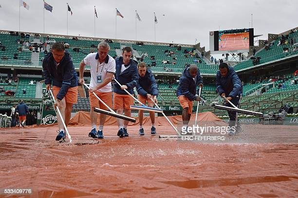 TOPSHOT Workers sweep the water off from the tarp covering the central court at the Roland Garros 2016 French Tennis Open in Paris on May 22 2016 /...