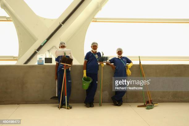 Workers take a break as they prepare the stadium at the Arena Amazonia on June 12 2014 in Manaus Brazil England play Italy in their group opening...
