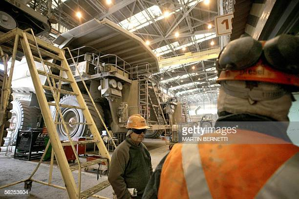 Workers take a break at the repair worshop of the gigantic Komatsu 930 330 metric tons lorries at the Chuquicamata copper mine in the desert town of...
