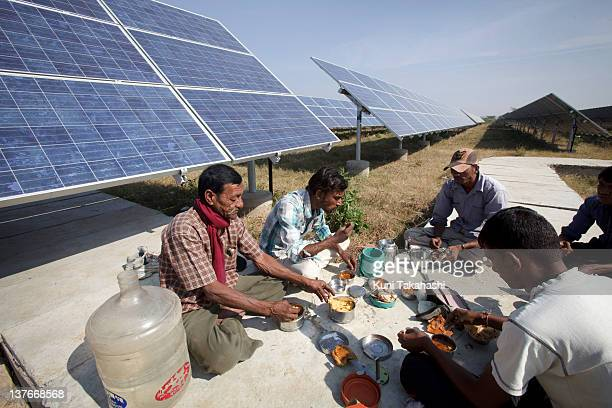 Workers take a lunch break from cleaning solar panels at the Azure Solar Plant on December 15 2011 in Khadoda Gujarat state India India plans to...
