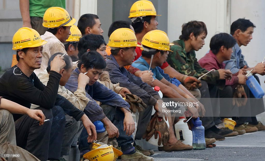 Workers take a rest outside a construction site in Shanghai, China, on Sunday, June 30, 2013. China's President Xi Jinping said officials shouldn't be judged solely on their record in boosting gross domestic product, the latest signal that policy makers are prepared to tolerate slower economic expansion. Photographer: Tomohiro Ohsumi/Bloomberg via Getty Images