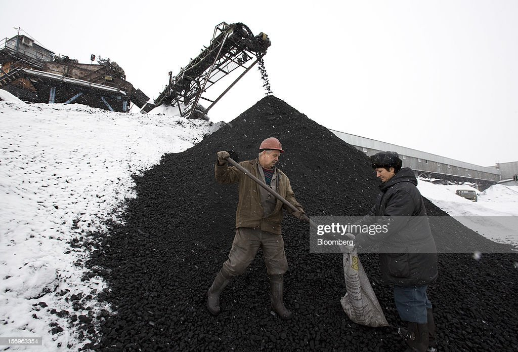 Workers take coal samples from a storage mound at the Sibirginsky open pit coal mine, owned by OAO Mechel and operated by Southern Kuzbass Coal Co., near Myski, in Kemerovo region of Siberia, Russia, on Friday, Nov. 23, 2012. OAO Mechel is Russia's biggest maker of steelmaking coal. Photographer: Andrey Rudakov/Bloomberg via Getty Images
