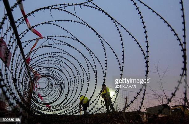 TOPSHOT Workers take meassurements of a near finished section of a 37 km long fence at a border crossing between Austria and Slovenia at Spielfeld...